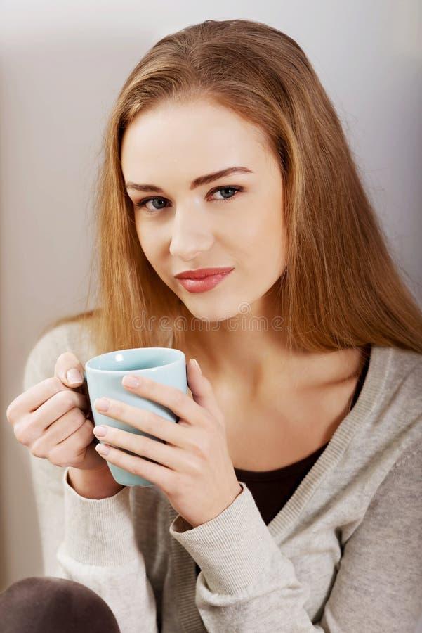 Schöne zufällige kaukasische Frau, die mit heißem Getränk sitzt. lizenzfreie stockfotografie