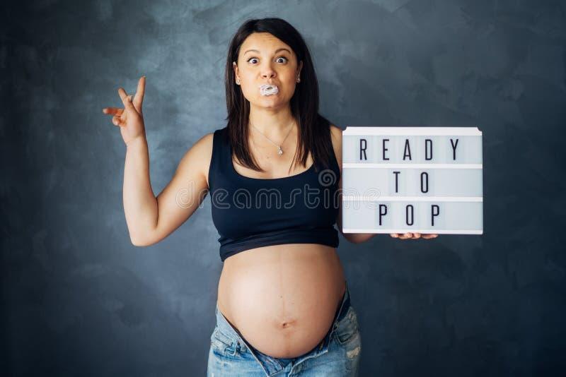 Schöne zukünftige Mutter, die mit dem Bauch im Anblick lächelt Schwangerschaftsbauch lizenzfreie stockfotos