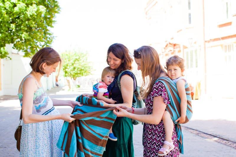 Schöne zukünftige Mutter, die Riemen, Babytrage betrachtet stockbilder