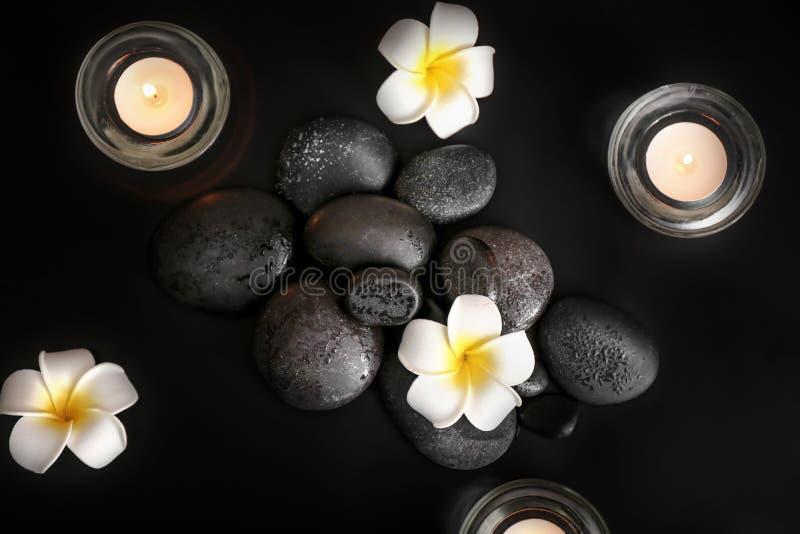 Schöne Zusammensetzung mit Badekurortsteinen, Blumen und brennenden Kerzen auf schwarzem Hintergrund, Draufsicht lizenzfreie stockfotos