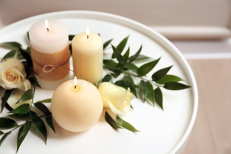 Schöne Zusammensetzung mit brennenden Kerzen und Blumen stockfotos