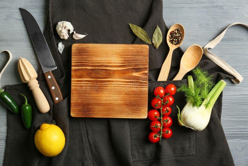 Schöne Zusammensetzung mit leerem hölzernem Brett und Gemüse Kochkurskonzept lizenzfreie stockfotos