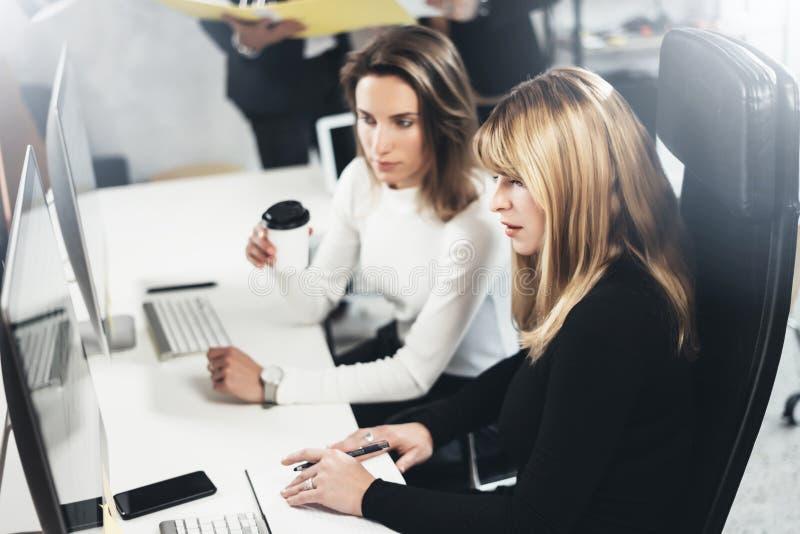 Schöne zwei Geschäftsfrau, die Gespräch in modernem lightfil Büro macht Hübsche Mädchen an Arbeitsprozeß horizontal lizenzfreies stockbild
