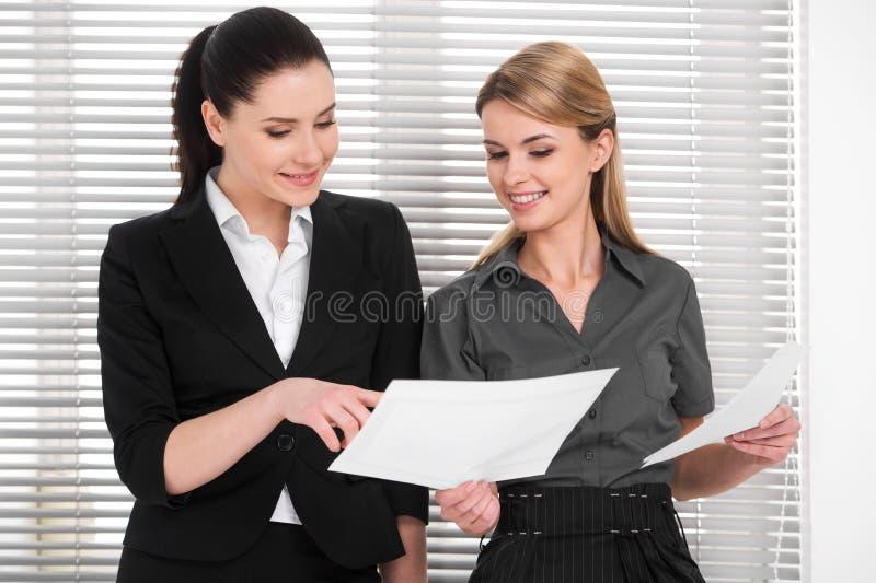 Schöne zwei Geschäftsfrau, die Ideen mit einander teilt. lizenzfreie stockfotografie