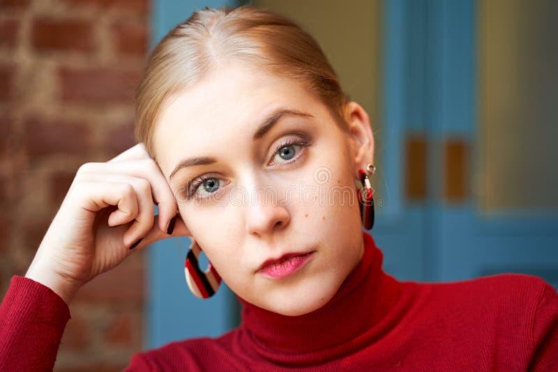 Schönen Blondine betrachten bedacht der Kamera, tragen eine rote Strickjacke und runden Ohrringe stockfotografie
