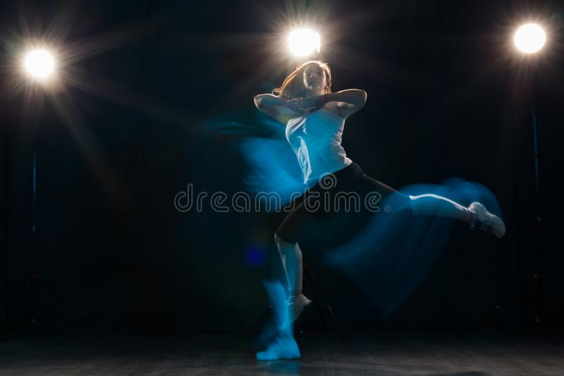 Schönen und der Leute Konzept des Tanzens, des Sports, - Tanzen der jungen Frau in der Dunkelheit sprang in buntes Licht lizenzfreie stockbilder