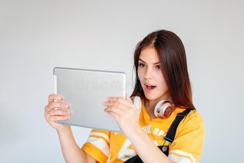 Schöner überraschter brunette Mädchenjugendlicher in der gelben T-Shirt Holdingtablette in den Händen, lokalisiert auf weißem Hin lizenzfreies stockfoto