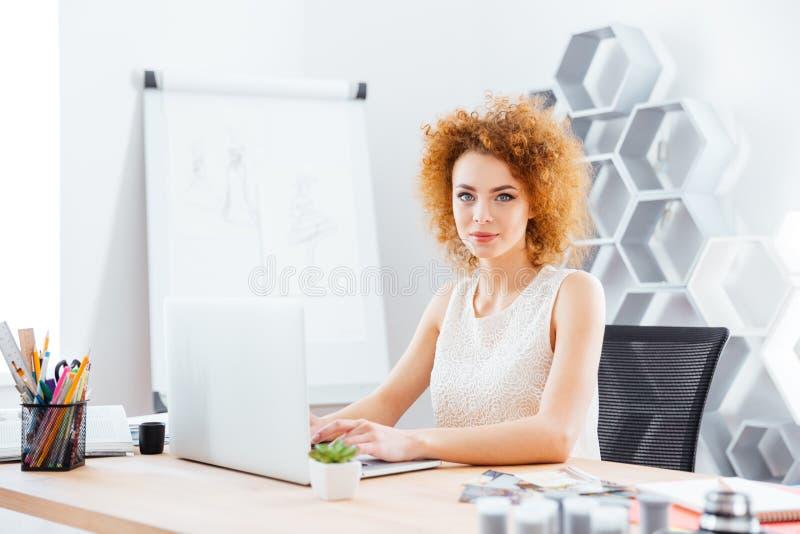 Schöner überzeugter Frauenmodedesigner, der Laptop im Büro verwendet lizenzfreie stockfotos