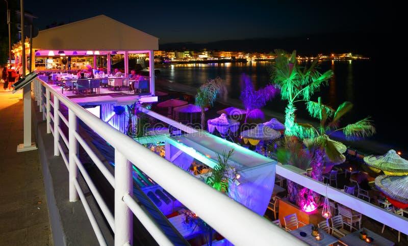 Schöner Abend mit dem Nachtufer mit einem Strand und Regenschirmen und mit heller colorsin Hersonissos-Bucht Kreta hervorgehoben lizenzfreie stockfotografie