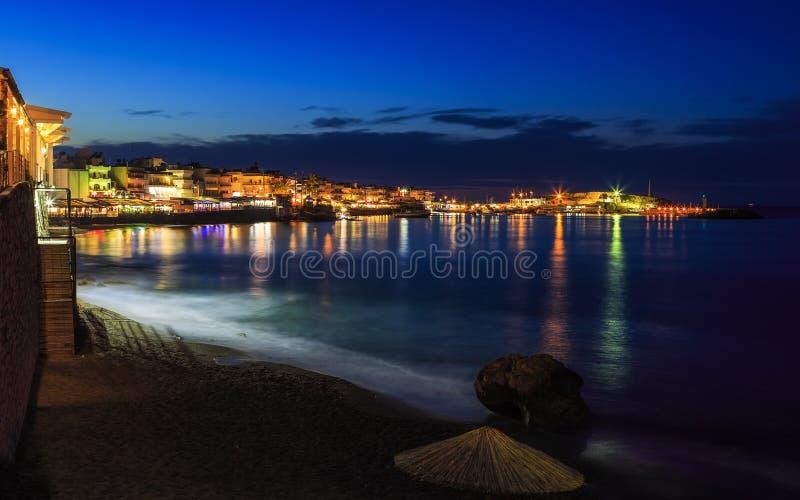 Schöner Abend mit dem Nachtufer mit einem Strand und Regenschirmen und mit heller colorsin Hersonissos-Bucht Kreta hervorgehoben stockfotos