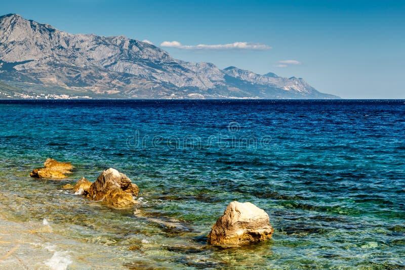 Schöner adriatischer Strand nahe aufgespaltet und Biokovo-Berge stockfotografie