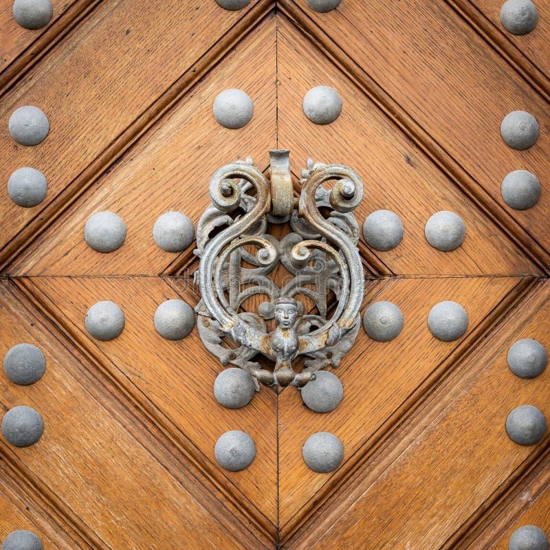 Schöner alter Türknauf hergestellt vom Silber auf einer braunen Tür stockfotografie