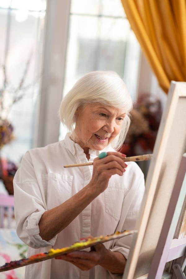 Schöner angenehmer gealterter Künstler, der beim Arbeiten erstaunlich sich fühlt stockfotos