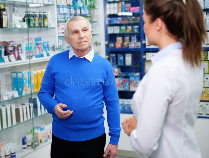 Schöner Apotheker der jungen Frau, der dem Kunden Drogen des älteren Mannes in der Apotheke zeigt lizenzfreies stockbild