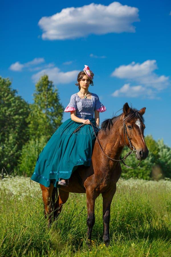 Schöner Aristokrat in einem Kleid auf einem Pferd lizenzfreie stockfotos