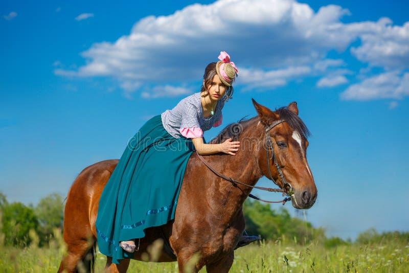 Schöner Aristokrat in einem Kleid auf einem Pferd stockfotos