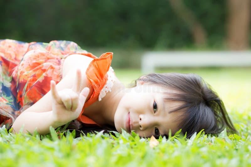 Schöner Asiat des kleinen Mädchens des Porträts eines lächelnden Lügens auf grünem Gras am Park stockbild