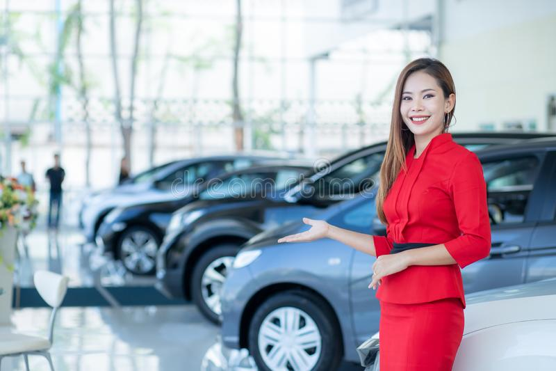 Schöner Asiatin- oder Autoverkäufer Stand, das einen Neuwagenfernschlüssel im Ausstellungsraum, Autos für Verkauf hält stockfotografie
