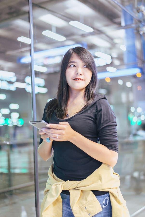 Schöner Asiatinreisender, der Handy im Flughafen, Lebensstil unter Verwendung des Handys verwendet lizenzfreies stockfoto