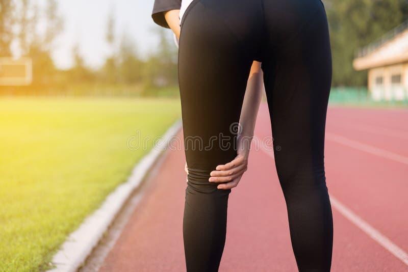 Schöner asiatischer Frauenläufer, der Knieschmerz und -verletzung nach laufend hat lizenzfreie stockbilder