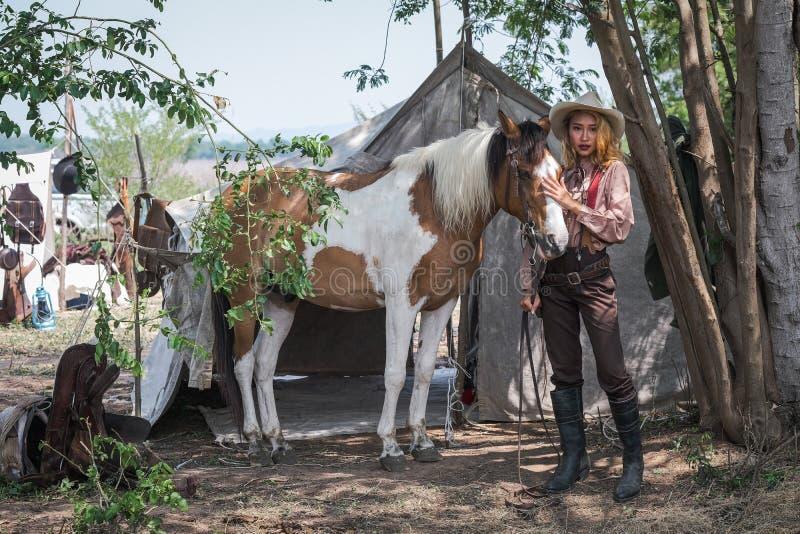 Schöner asiatischer Mädchencowboy kümmert sich um ihrem Pferd mit Liebessorgfalt stockfotos