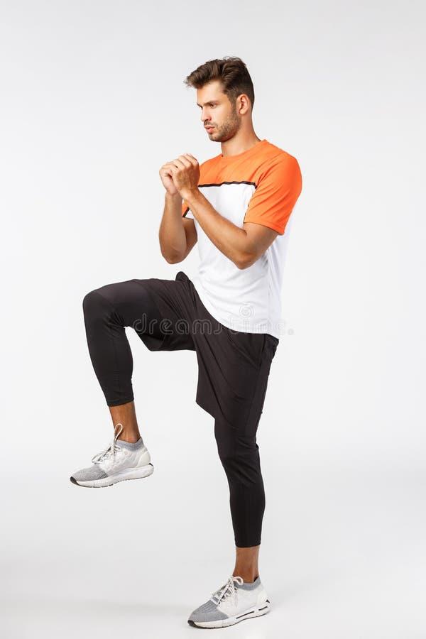 Schöner bärtiger junger männlicher Sportler in Shorts, Leggings und Sport-T-Shirt, Clench-Arme, schaffen Spannung, trainieren im  lizenzfreies stockbild