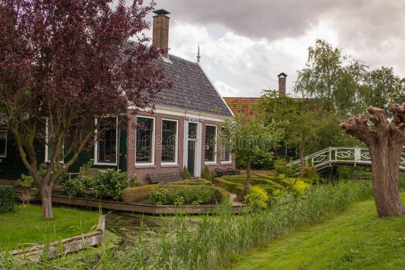 Schöner Backsteinbau mit Brücke und Bäume durch den Fluss Idyllische Landschaftslandschaft Wohnsitz mit Garten nahe Kanal stockfotografie