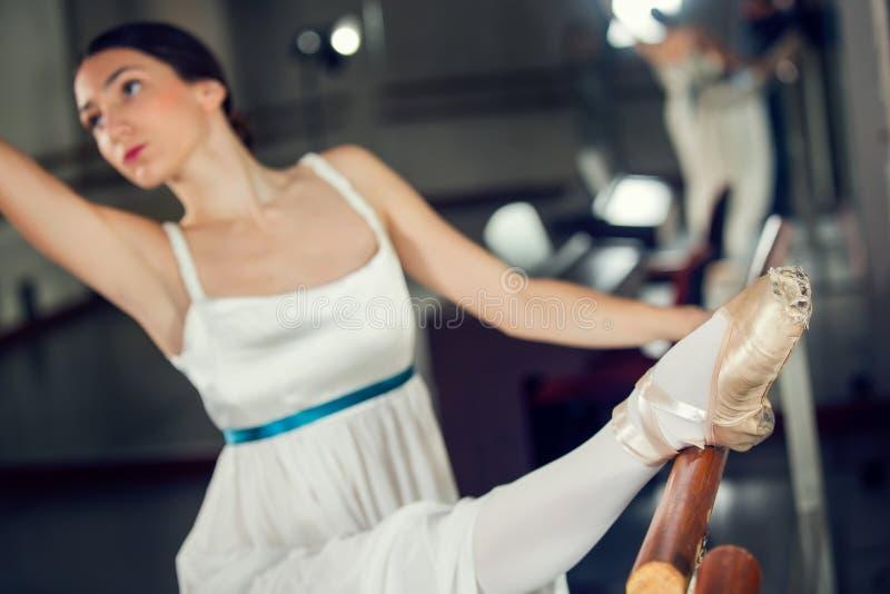 Schöner Balletttänzer im weißen Ballettröckchen, das auf einem Bein nahe bei Handgriff aufwirft stockbild