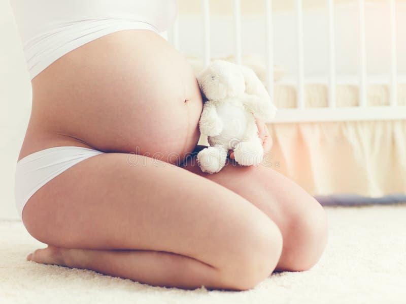 Schöner Bauch der schwangeren jungen Frau, die auf Teppich im nur sitzt lizenzfreies stockbild