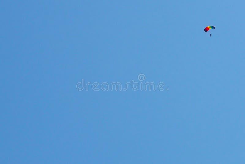Schöner blauer Himmel an einem wolkenlosen Tag Und ein buntes Fallschirmspringen in den Himmel Für Hintergrund stockfotos