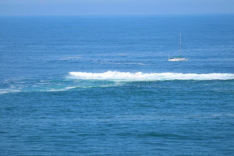 Schöner blauer Ozean mit den zusammenstoßenden Wellen und einer weißen Yacht lizenzfreie stockfotografie