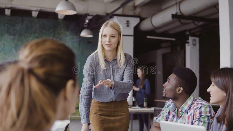 Schöner Blondinemanager, der dem multiethnischen Team Richtung gibt Kreatives Geschäftstreffen im modernen Hippie-Büro lizenzfreie stockfotos