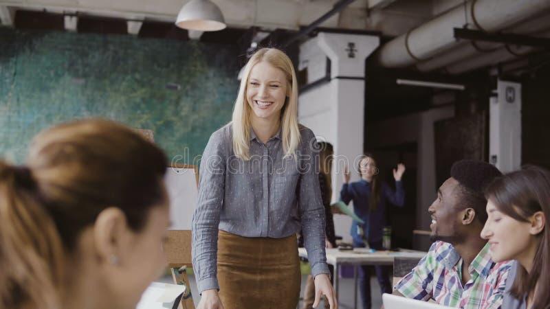 Schöner Blondinemanager, der dem multiethnischen Team Richtung gibt Kreatives Geschäftstreffen im modernen Hippie-Büro stockbilder