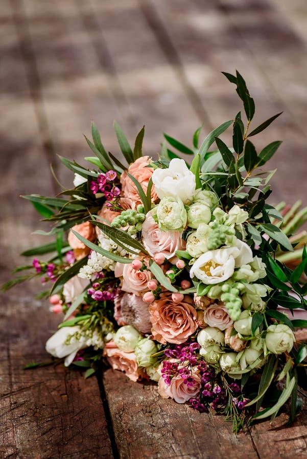 Schöner Blumenstrauß der Braut auf einem hölzernen Hintergrund lizenzfreies stockbild