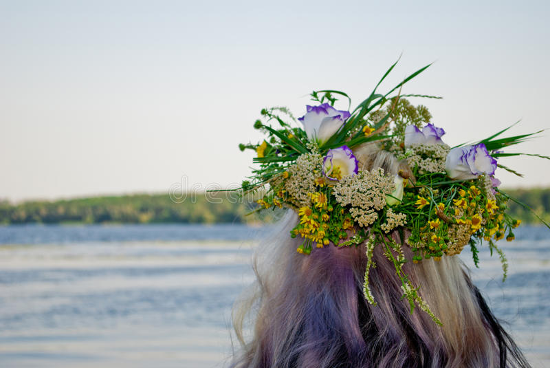Schöner Blumenstrauß des Kranzes der wilden Blumen auf dem Mädchenkopf nahe dem Wasserfluß stockbild