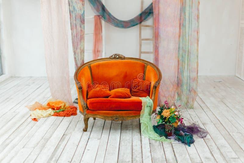 Schöner Blumenstrauß in einer modernen Art, stehend nahe dem orange Sofa stockfoto