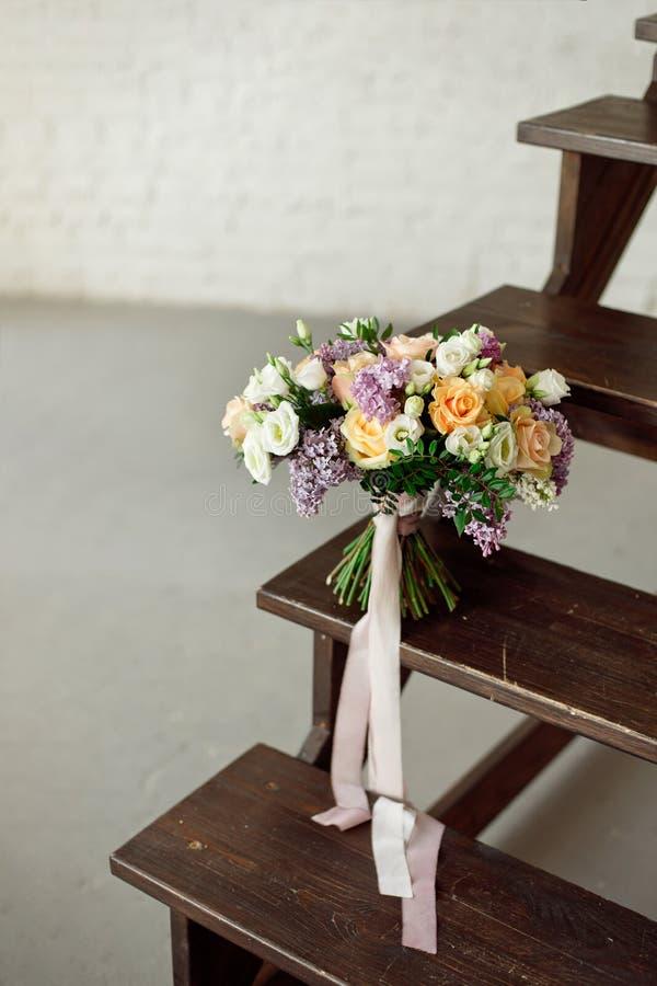 Schöner Blumenstrauß von Blumen von Rosen und von lila Ständen auf einer hölzernen Leiter gegen eine weiße Backsteinmauer lizenzfreie stockfotos