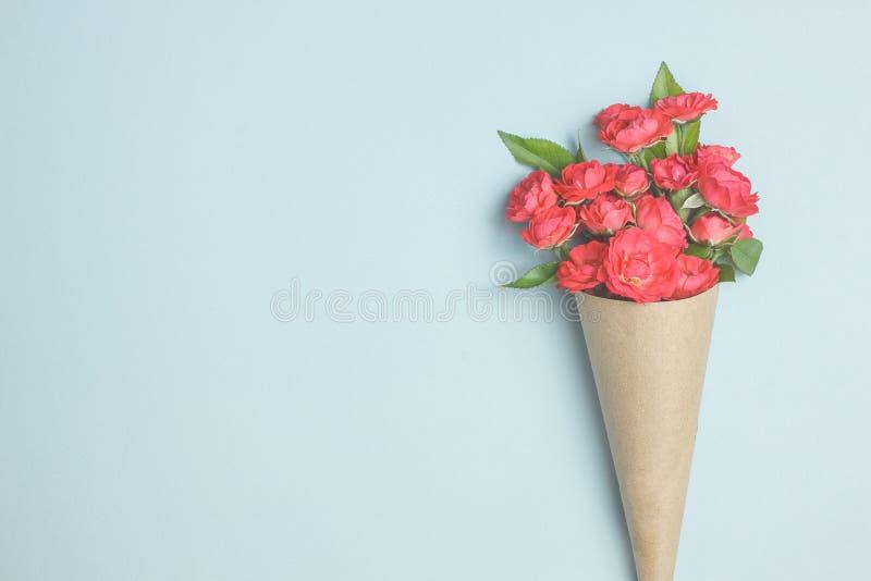 Schöner Blumenstrauß von kleinen roten Rosen im Weinlesepapier auf dem Tisch lizenzfreie stockfotos