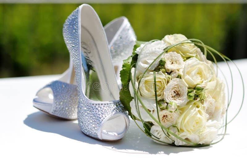 Schöner Blumenstrauß von Rosen und von Hochzeitsschuhen lizenzfreie stockfotos