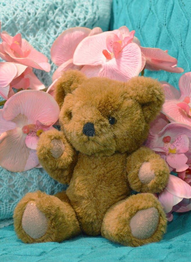 Schöner brauner Teddybär mit rosa Blumen stockbilder
