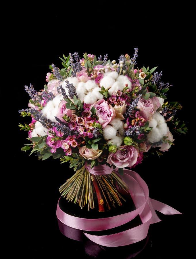 Schöner Brautblumenstrauß mit Rosen und Baumwolle auf Schwarzem stockfotografie