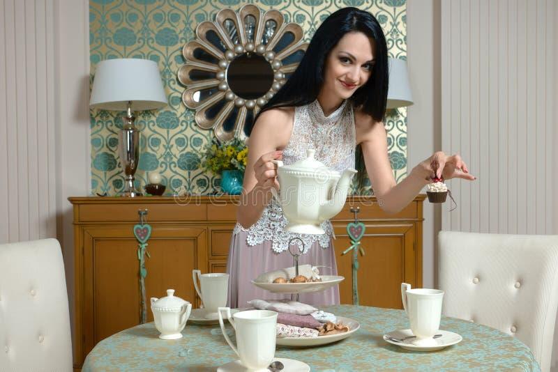 Schöner Brunette bietet es einem Geschmack die Kappe des Tees an stockfotos