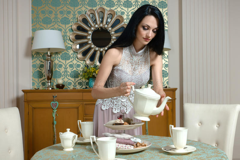 Schöner Brunette bietet es einem Geschmack die Kappe des Tees an lizenzfreies stockfoto