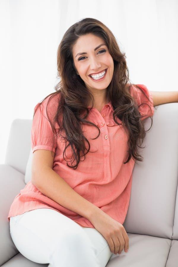 Schöner Brunette, der auf ihrer Couch lächelt an der Kamera sitzt stockfoto