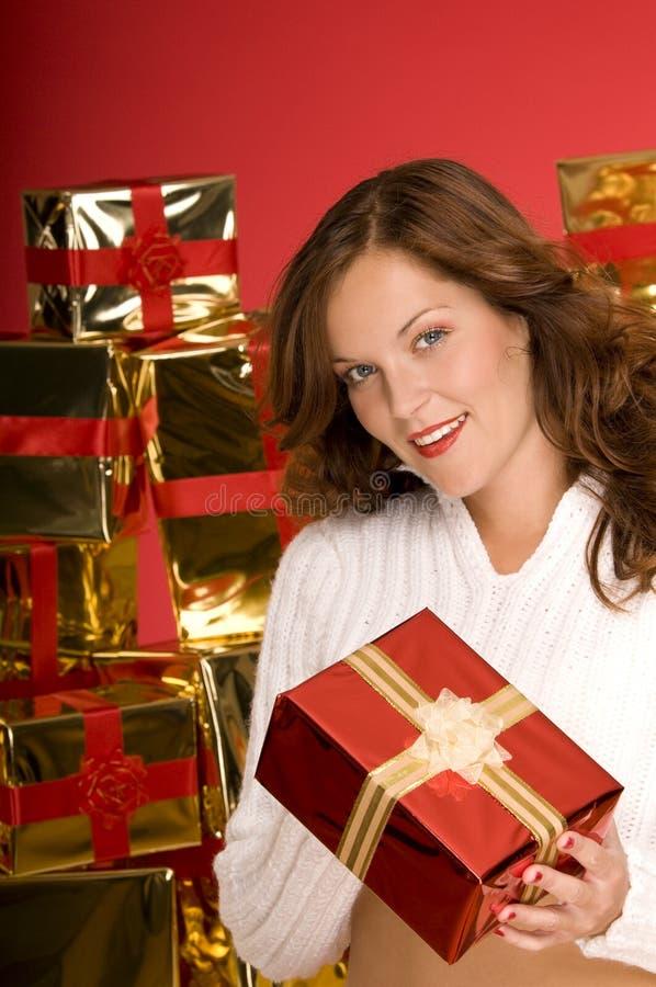 Schöner Brunette, der ein Weihnachtsgeschenk anbietet stockfoto
