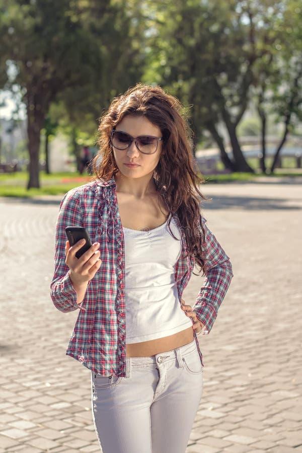 Schöner Brunette, der eine Mitteilung vom Telefon liest stockfotografie