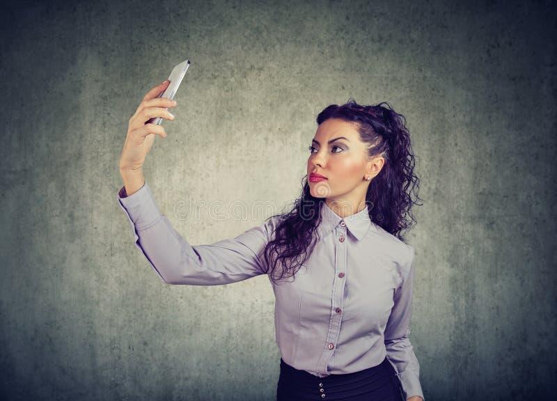 Schöner Brunette in der formalen Ausstattung unter Verwendung des Smartphone und nehmen selfie auf grauem Hintergrund lizenzfreie stockfotos