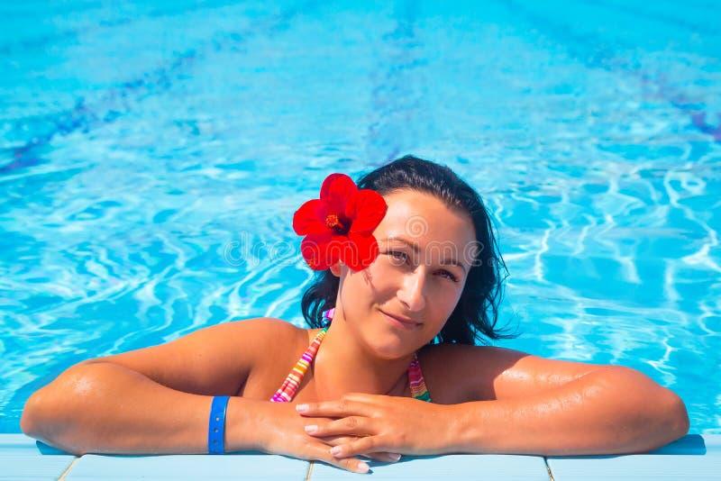 Schöner Brunette, der am Swimmingpool sich entspannt stockbilder