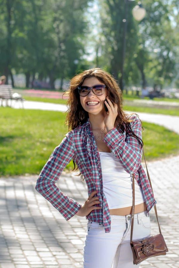 Schöner Brunette, der am Telefon spricht lizenzfreie stockfotografie