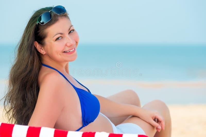 Schöner Brunette in einem deckchair ein Sonnenbad nehmend stockbilder